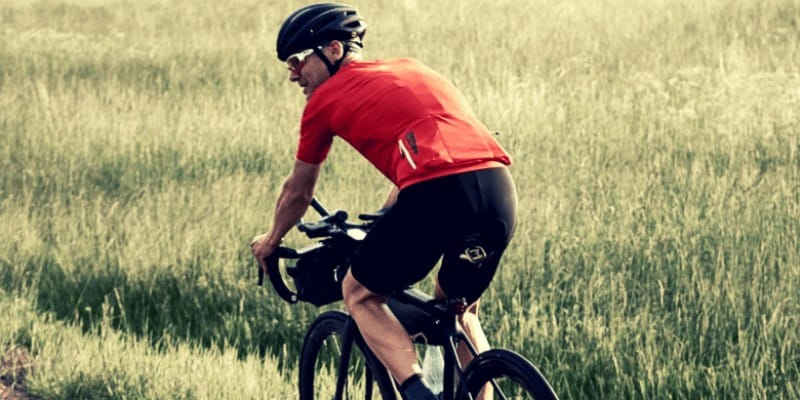 Man with a red shirt riding a road bike