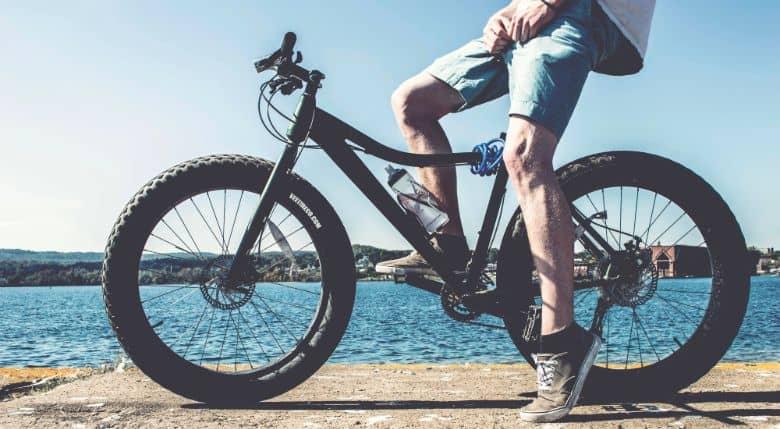 Man on black fat bike on brown concrete platform overlooking body of water at daytime