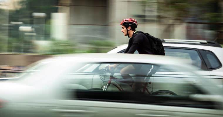 Man avoiding traffic because he is riding on a bike
