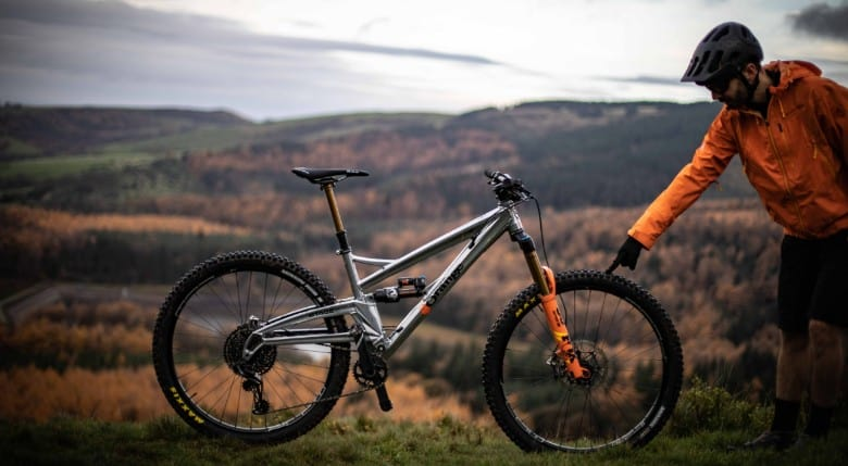Person with a orange jacket pointing his vinger at a mountain bike wheel