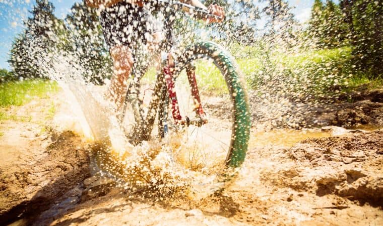 All-mountain bike hardtail with front suspension in full action racing through the mud