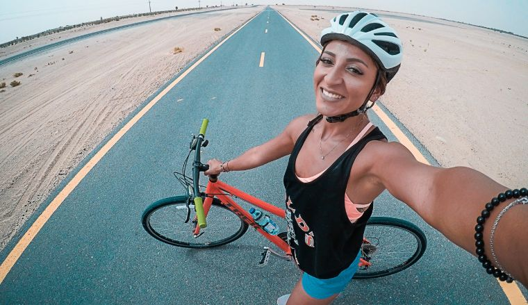 Woman making selfie with oad and bike on background
