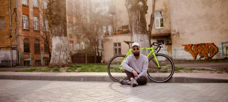 College student sitting in front of his road bike.