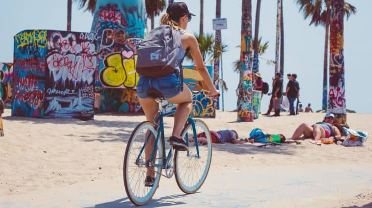 A female college student is riding on one of the best bikes for college students, near the beach.
