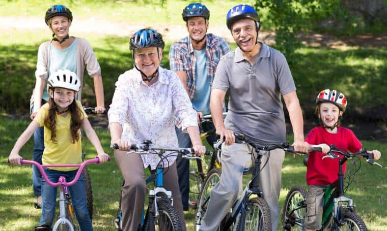 Family of two seniors on bikes wearing bicycle helmets