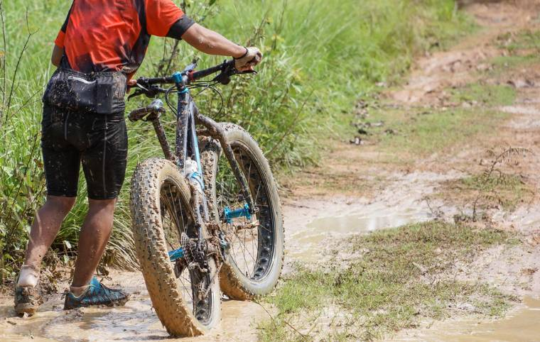 Person rding a fat tire bike in muddy terrain
