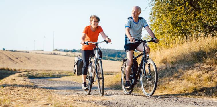 Two older people riding a comfort bicycle for seniors