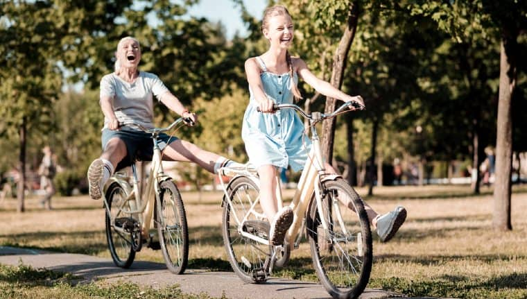 Two smiling women riding on comfort bicycles