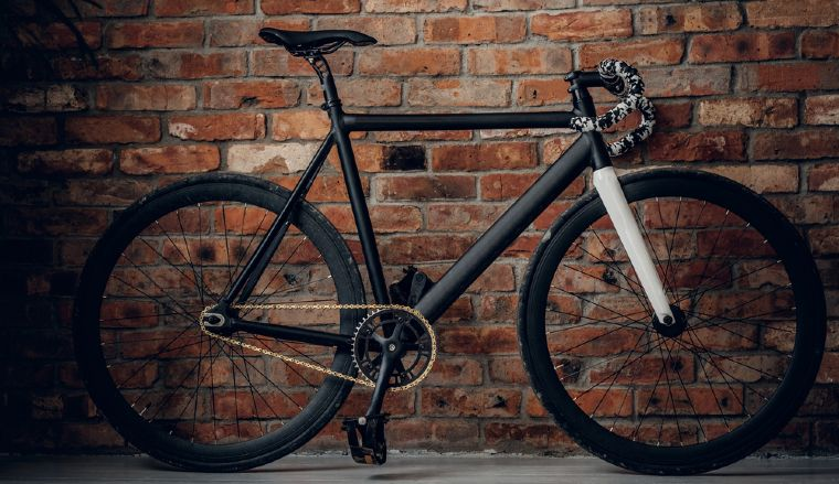 Black Fixed Gear Bike Next to a Brick Wall